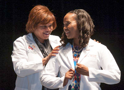Alexis Bagwell receives coat fro Sheryl Allen, M.D.